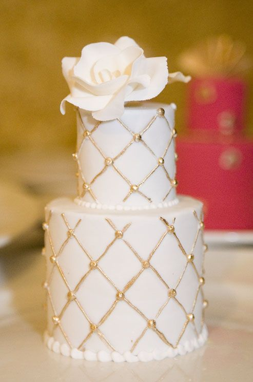 Gold quilting and a white rose dress up this miniature wedding cake.