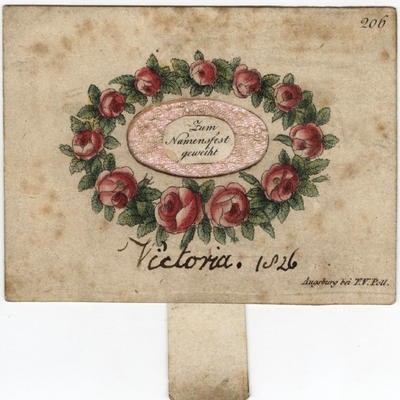 """A name day card signed by Queen Victoria as a child is inscribed with a message in German: """"My wish for you is the most beautiful luck and happiness."""" A tab pulls to reveal a pink gauze centre and the words in German: """"Presented on your name day."""""""