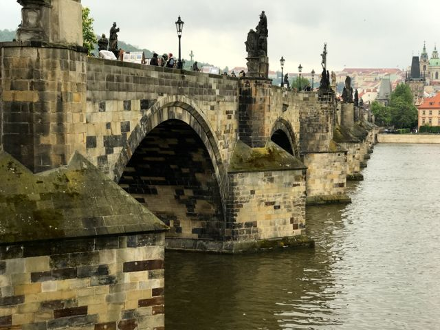 07 de maio de 2017 Uma das maiores atrações da cidade de Praga, é a Ponte Carlos. Saindo da praça central da Cidade Velha, seguimos andando pela estreita e sinuosa Rua Carlos, que segue sempre lota…