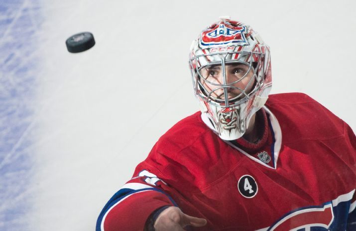 Montreal Canadiens goaltender Carey Price tosses a puck to fans after defeating the San Jose Sharks in an NHL hockey game, Saturday, March 21, 2015 in Montreal. (AP Photo/The Canadian Press, Graham Hughes)