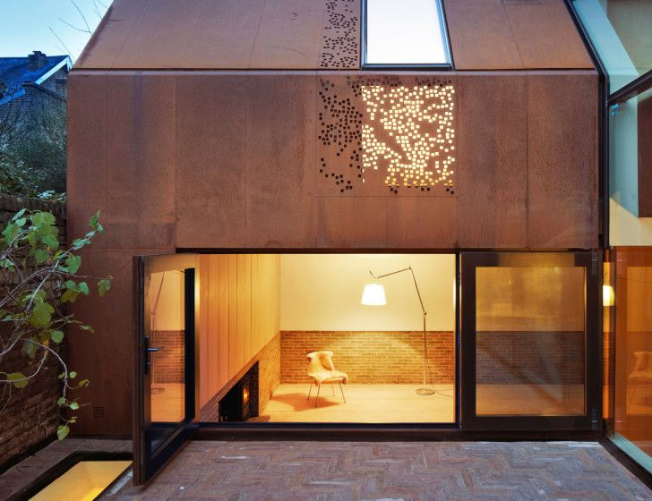 Natural light flows into the house through the glass-enclosed passageway and large windows, as well as through the perforations in the orange-toned weathered steel that create beautiful dappled light effects evoking an autumnal palette.