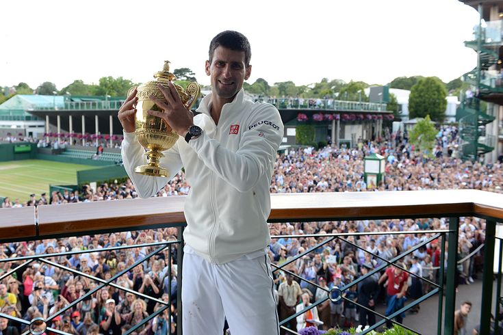 Novak Djokovic holds the Gentlemen's Singles Trophy with a crowd of fans in the background - Tom Lovelock/AELTC