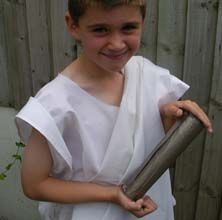 A photograph of a boy dressed in a toga holding a scroll