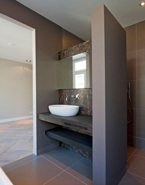 Dit is een open badkamer met veel bruin tinten. Het blad is van een donker hout kleur gemaakt met daar op een witte ovale kom. In het blad is een gleuf gecreëerd om een handdoek te kunnen ophangen.  #design #inspiration #bathroom #shower #badkamer #bath #hotbath #porcelanosa #gjmeijer #meijer #tegels #tiles #hansgrohe