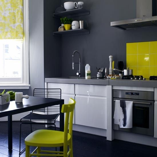 Charcoal grey walls make a dramatic statement in this kitchen. A zingy yellow splashback and matching chair give it an eclectic edge, while the floral blind adds a welcome touch of colour.