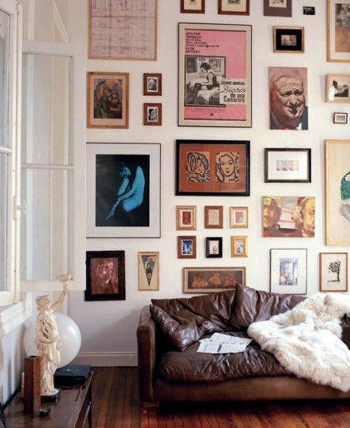 Kunst aan de muur: Nog altijd de perfecte manier om een ruimte in één keer op te fleuren: veel posters, foto's en afbeeldingen aan de muur. De oude leren bank op deze foto steekt zo lekker af tegen de muur.