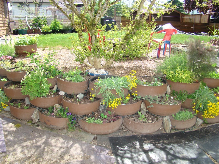 TIRES! Planting Retaining Wall. Tire tops are cut off and tires are flipped inside out so they look smooth. Then painted with latex house paint. Very nice and cheap retaining wall. Large tire recycling places will PAY YOU to take tires away too. But local tire shops will sell you old ones.