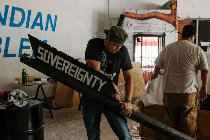 Remy, center, an artist from the Navajo Nation in Black Mesa, Arizona, and Wiyaka Eagleman, who is from the Rosebud Sioux Reservation in South Dakota, work on a covered wagon they will use in Washington, D.C., during the People's Climate March on Saturday.
