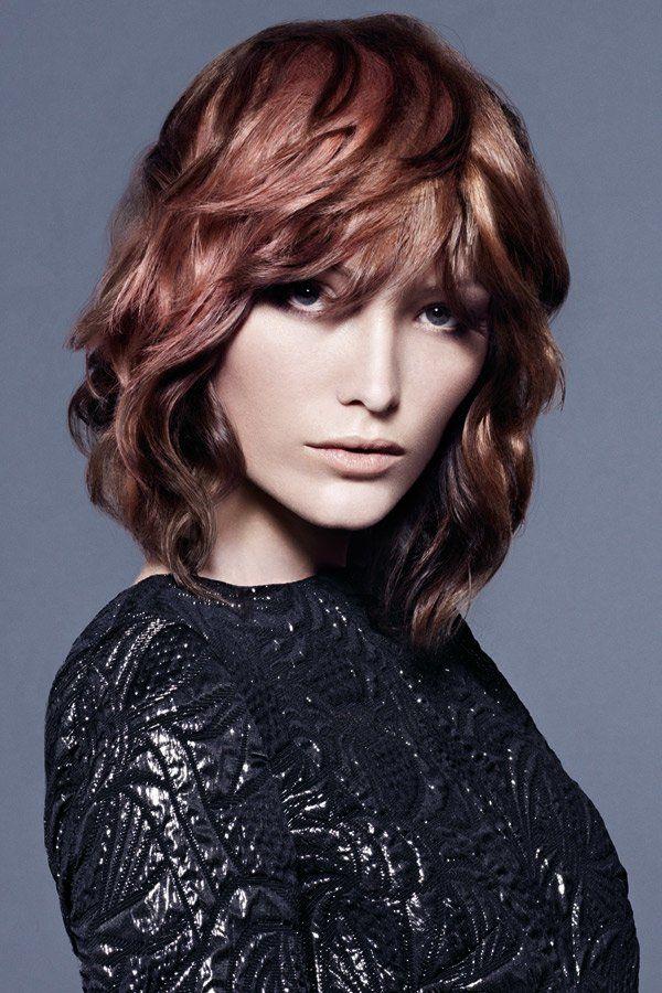 Der perfekte Schnitt für welliges Haar spielt mit verschiedenen Nuancen von Rotbraun und ist stufig geschnitten.Noch mehr Frisuren mittellang hier
