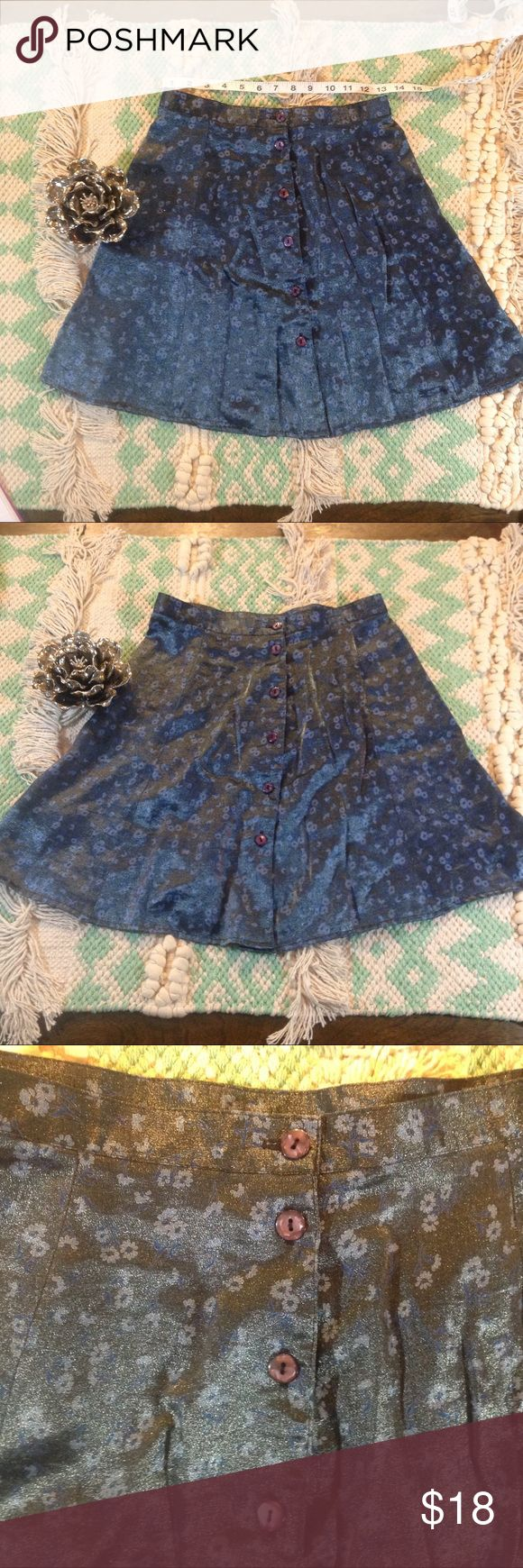 """Vintage Iridescent Button-up High-waisted Skirt! This lovely little 90's number is by ExactChange. It is made of this magical iridescent floral fabric that seems to change colors with the light. In person, it is more dark silver than the pictures suggest. The flowers are two-toned blue, though. It's an A-line, high-waisted style with purple buttons down the entire front. States is a Size 7 but I think it would fit a Small or XS. Laying flat: waist 13"""", length 18"""". Vintage Skirts Mini"""
