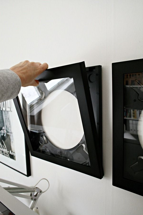 Record frames that open up while staying on the wall.