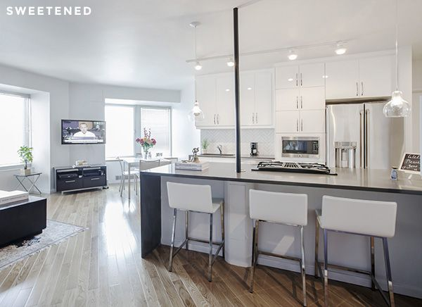 Open plan Midtown kitchen features a white and gray color scheme and an island fitted with gray caesarstone countertop with waterfall edge.