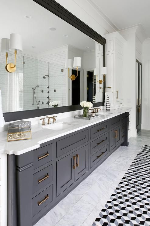 Barbara Barry Go Lightly Sconces are fixed to a full length black framed vanity mirror hung above a black dual washstand boasting shaker cabinets with bras pulls.