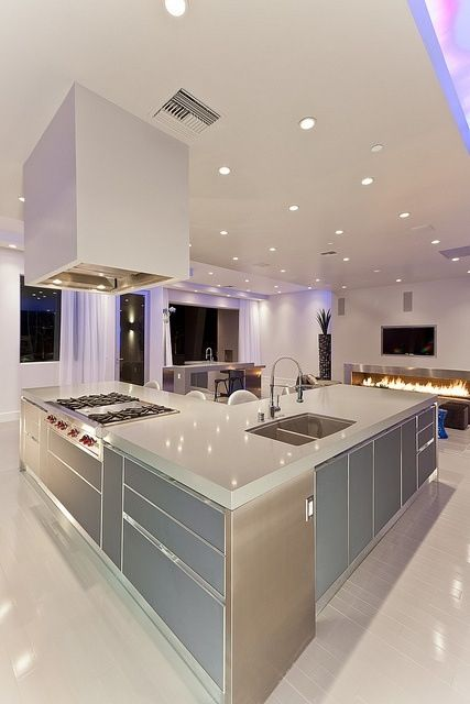 Minimalist solid surface kitchen with punches of color from lighting.