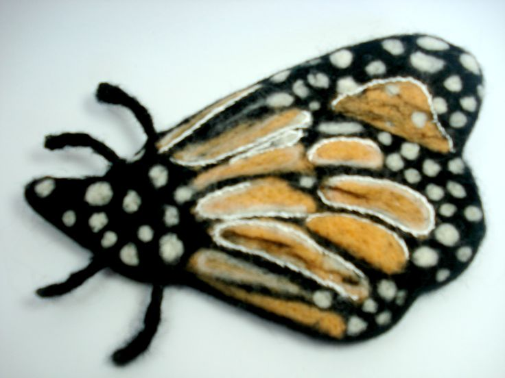 Needle felted butterfly over a thick piece of wool felt