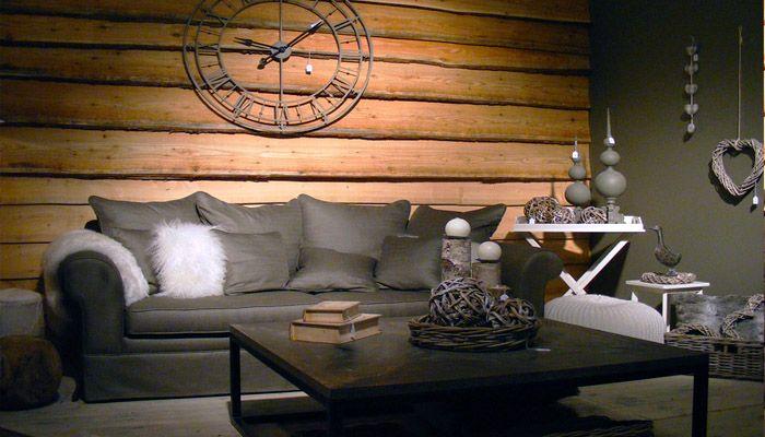 landelijke woonkamer met grijze stoffen zetel en houten achterwand