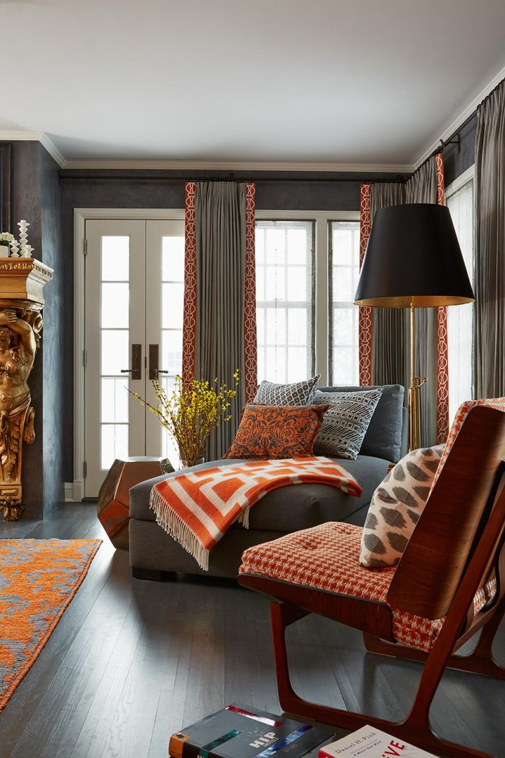 Splashes of orange bring vibrant energy to this charcoal gray bedroom. Mixed patterns create eye-catching interest within the sitting area.