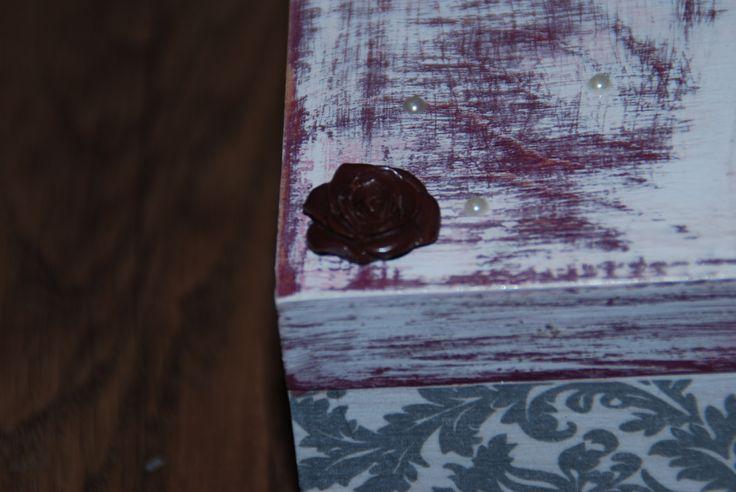 Zbliżenie na motywy zdobnicze - perełki i gliniany kwiatek.