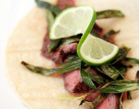 Garlic-Marinated Skirt Steak Tacos with Cebollitas Asadas and Lime.