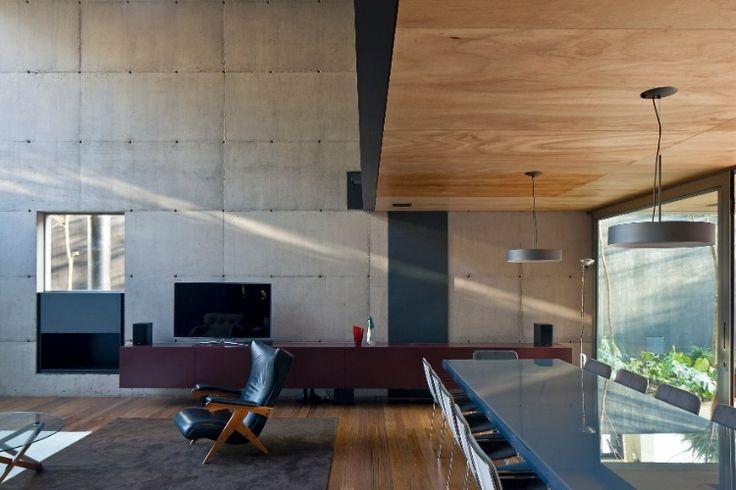 A parede estrutural em concreto aparente concede um ar contemporâneo aos interiores da Casa Bacopari, projetada pelos arquitetos do Grupo Una. Estar e jantar - integrados e voltados para o exterior através de amplos panos de vidro - possuem ambientação com peças de família, como a poltrona preta (ao centro do ambiente); além de mesa e cadeiras de jantar da OVO e do móvel-aparador vinho, desenhado pelo escritório e executado pela Marcenaria da Fazenda