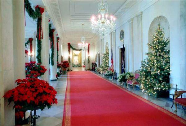 Étoiles de Noël autour du tapis rouge et guirlandes vertes décorées de rubans rouges
