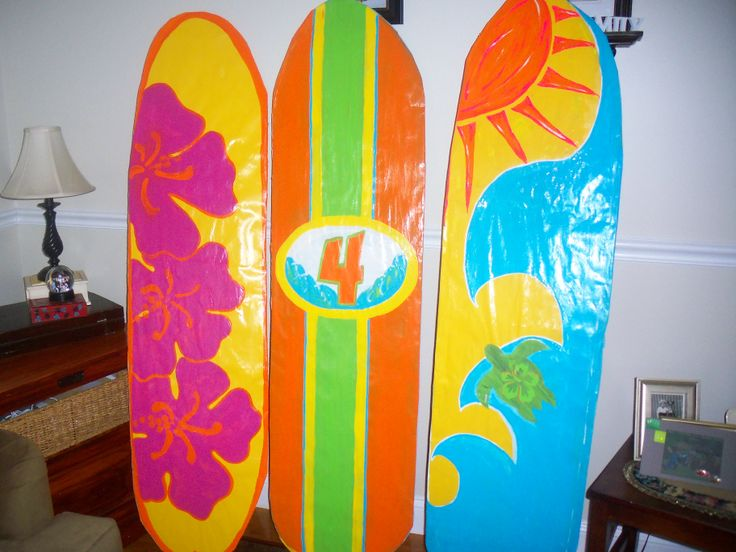 """3 of the 4 """"surfboards"""" I made for the 4th grade's Rock N' Roll Forever Show. Painted bulletin board  paper, cut out cardboard-pieced together, covered backs with more paper. Used Gloss Mod Podge for the shine and hot glued tops of cardboard egg crates for hand grips on the back to make it easier for the kids to carry on stage."""