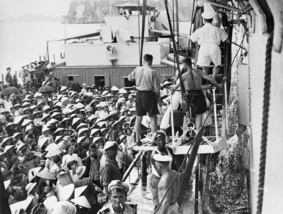 The aircraft carrier HMS WARRIOR evacuates 1,455 refugees from Haiphong, North Vietnam to Saigon during Operation PASSAGE TO FREEDOM, 4 September 1954. Refugees transfer from a French LCT landing craft to HMS WARRIOR at the port of Haiphong.