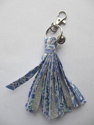 Porte-clé pompon réalisé en biais cousu au fil argenté, dans les tons robleus et argenté, liberty D'Anjo bleu. Modèle unique, hauteur environ 12 cm. Un mousqueton et un gre - 11467833