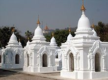 "World's Largest Book stands upright, set in stone in Mandalay. Each page is 3-1/2 ft wide, 5 feet tall, 5"" thick. Each stone tablet has its own roof and precious gem on top in a small cave-like structure."