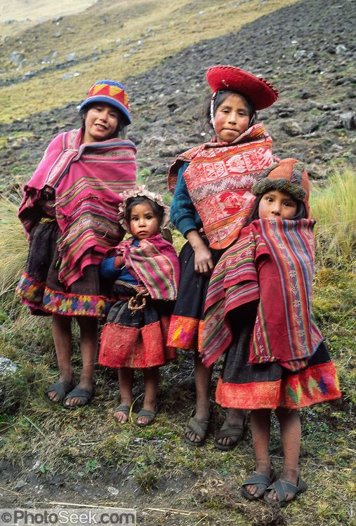 Four Andean mountain children dress in traditional red ponchos in the Cordillera Urubamba, Andes highlands, Peru