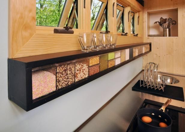 The need for a pantry was reduced by creating a food cube shelf that not only holds 18 cubes of food, but also houses the kitchen's electrical outlets and LED strip lighting. Kitchen appliances, including the stovetop, are all plug-in and can be stowed away, leaving more open counter space.