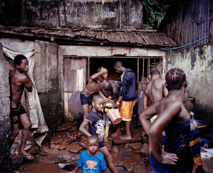 Fotoğraf: Mustafah Abdulaziz (Amerika Birleşik Devletleri)  Profesyonel Komisyon finalisti: 1.'lik ödülü Freetown, Sierra Leone'deki Kroo Körfezi'ndeki iki su kaynağından birinde yıkanan çocuklar. Bölgede temiz suya erişim yok.