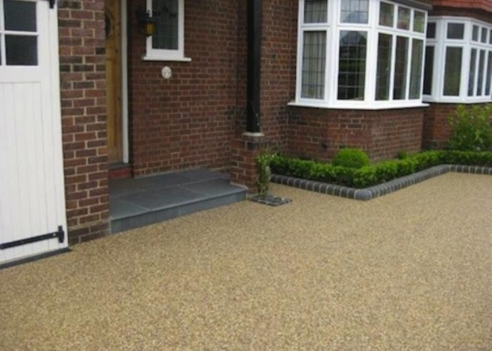 Resin Bound Gravel driveway Driveway - 20mm chocolate buff gravel  Edging kerbs - charcoal bull-nose (Brett)  Threshold - reclaimed blue clay bricks  Porch step - grey slate slab/tiles.  Resin Bound Gravel driveways provide a permeable solution.