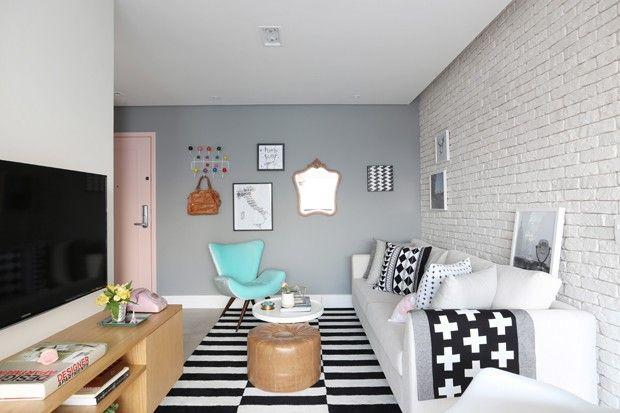 Uma das paredes chama a atenção por ser toda revestida de tijolos. Tapetes, almofadas e capas exibem diferentes padronagens em preto e branco - destaque da manta em cruzeta jogada sobre sofá, típica dos lares escandinavos. Telefone sobre rack e design do rack