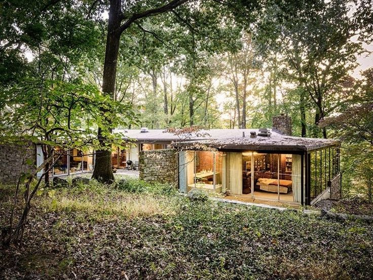 Richard Neutra's 1962 Pitcairn House has clean lines, stone walls, walls of glass, simple furniture and is set in a surrounding forest.