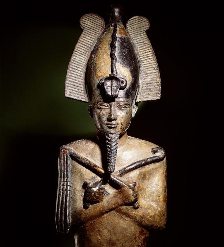 Osiris was de koning van de Egyptische onderwereld. Hier is hij te zien in de gedaante van een mummie, zoals hij vaak werd afgebeeld. Op zijn hoofd draagt Osiris de hoge Opper-Egyptische kroon met uraeusslang. In zijn gekruiste armen draag hij de heka en nekhakha, de kromstaf en de vlegel, ook de symbolen voor de macht van de farao.