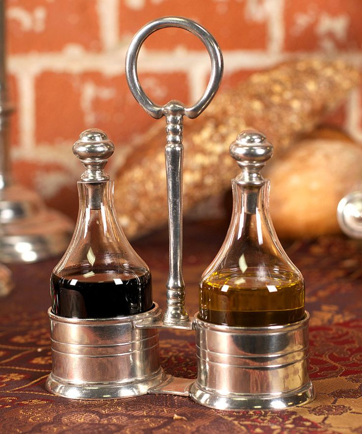 Classic Olive Oil and Vinegar Set - Pared-down design with subtle horizontal banding looks flawless on your table whether it's a casual addition to a breakfast nook or a reliable standby for serving formal Mediterranean meals to a grand group. The transitional sleekness of the Classic Olive Oil and Vinegar Set in glass and pewter extends to the repeated circular motif of its stoppers and carrying loop.
