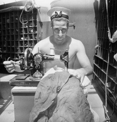 A British sailor uses a sewing machine to repair a signal flag on board the armed merchant cruiser HMS ALCANTARA en route to Sierra Leone, 1942  Beaton, Cecil  © Crown Copyright: IWM (CBM 1049)