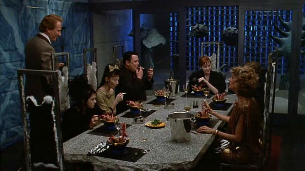 Beetlejuice set design, the modern blue, black, grey, & stone dining room after Lydia Deetz remodels the Connecticut Farmouse. 1980s modern design comically exaggerated but spot-on at the same time