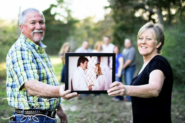 Parents holding their wedding photo with their family in the background.