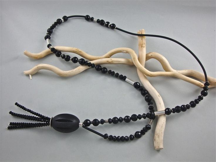 Schwarze facettierte Glas Perlen in schwarz mit Kautschukband und versilberte Metall Zwischenteile. Die Kette endet mit einer Holz Perle und daran ans
