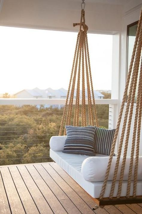 Chic covered second floor balcony is fitted with a rope swing bed adorned with plush white cushions and blue striped pillows.