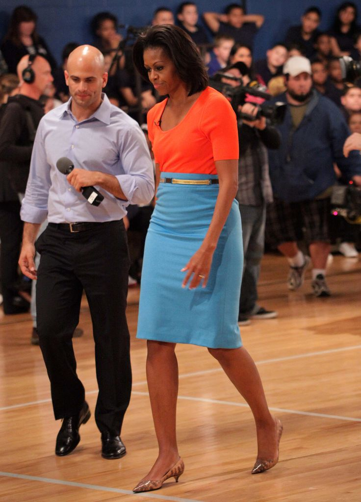 Michelle brought a cheery colorblocked look to her Let's Move campaign event. She paired an orange scoop-neck top with a bright blue pencil skirt, cinched at the waist with a thin white belt.
