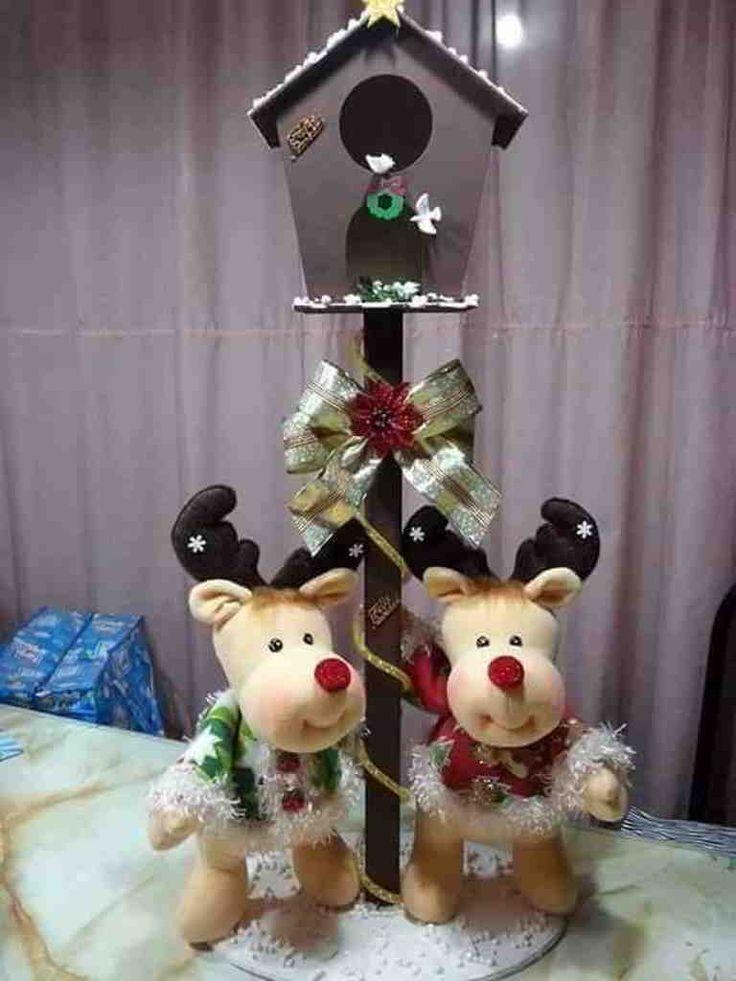 Tierna pareja de renitos navideños, que están visitando una hermosa casita para aves en un día de invierno. Los renitos se ve bien rellenitos, como si fueran unos niños que llevan abrigos muy bien acolchados para contrarrestar el crudo invierno.