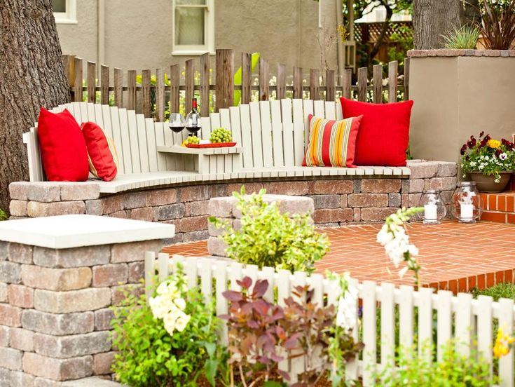 Enjoy some wine and grapes on this brick patio with built-in seating accented by vivid throw pillows. Candles and a container of flowering plants add to the coziness.