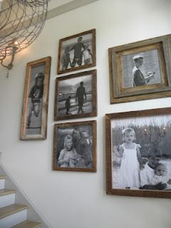 Collection of black and white family pics in rustic frames line the hall... smart!