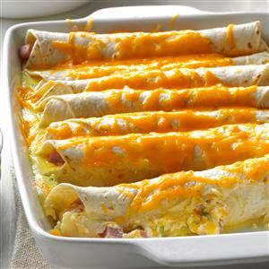 Brunch Ham Enchiladas Recipe -When I'm expecting company for brunch, the menu often features this tried-and-true casserole. With ham, eggs and plenty of cheese, the enchiladas are flavorful, hearty and fun. Plus, they can be easily assembled the day before. -Gail Sykora, Menomonee Falls, Wisconsin