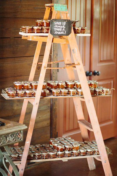 Pourquoi ne pas réinventer son échelle en présentoir pour de petits délices à partager avec vos invités ? Pour un mariage convivial et champêtre laissez à dispositions des confitures ou pots de miels pour remercier vos invités. Du bois clair et sans fioritures la table sera charmante tout en simplicité !