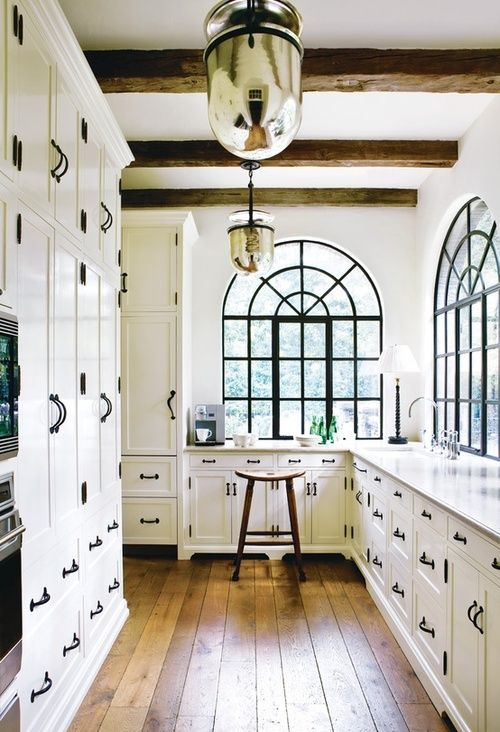 black hardware + rustic wood floors + arched windows =great kitchen space.