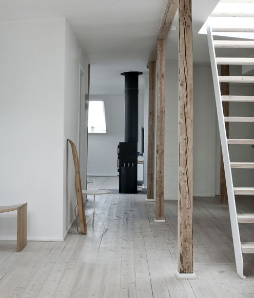 loft. wood stove, exposed aged supports, all of the white ... pretty :)